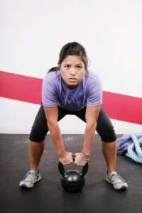girl lifting kettlebell at gym